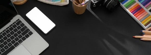 Vista superiore del piano di lavoro moderno scuro con lo smartphone, il computer portatile, i rifornimenti del progettista e lo spazio della copia
