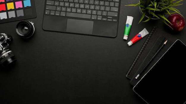 Vista dall'alto della scrivania da ufficio scuro con spazio di copia, tablet, tastiera, cancelleria, fotocamera, mock up creativa scena