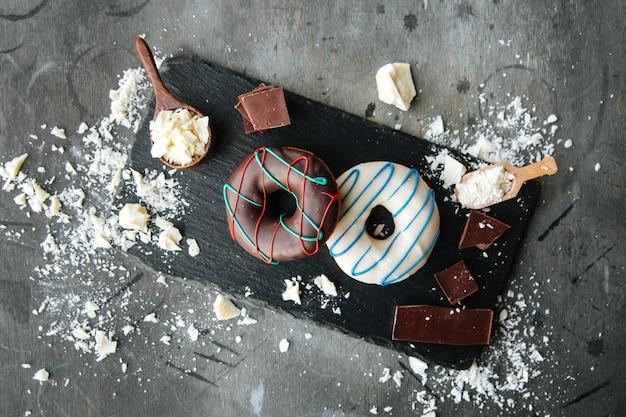 Vista dall'alto su ciambelle glassate al cioccolato fondente e bianco