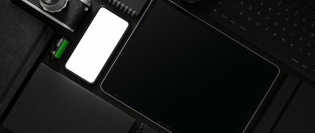 Vista dall'alto dell'area di lavoro scura con forniture per smartphone, tablet e fotografo