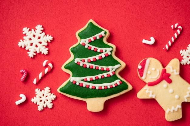 Vista dall'alto dei biscotti di panpepato di natale decorati su sfondo rosso della tavola con spazio per le copie, concetto di celebrazione delle vacanze.