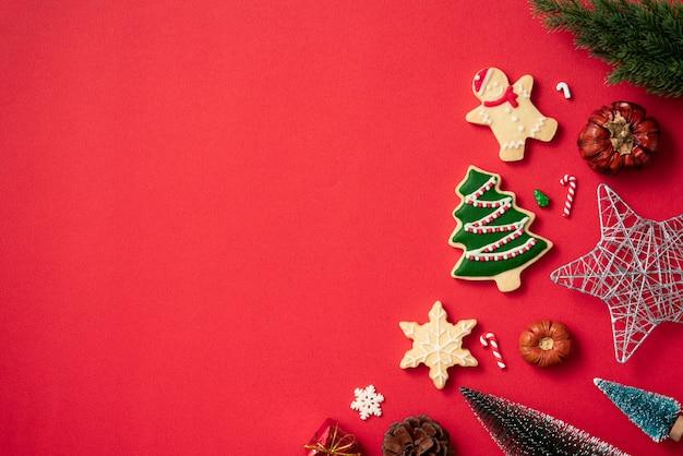 Vista dall'alto dei biscotti di panpepato di natale decorati con decorazioni su sfondo rosso della tavola con spazio per le copie, concetto di celebrazione delle vacanze.