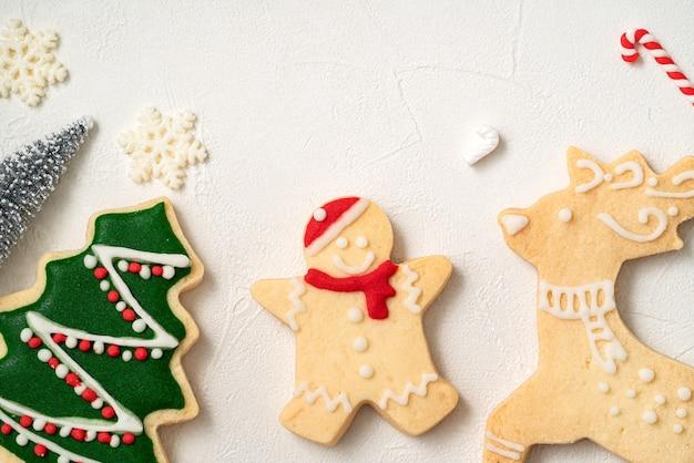 Vista dall'alto di biscotti di panpepato di natale decorati con decorazioni su sfondo bianco tavolo con spazio copia, concetto di celebrazione delle vacanze.