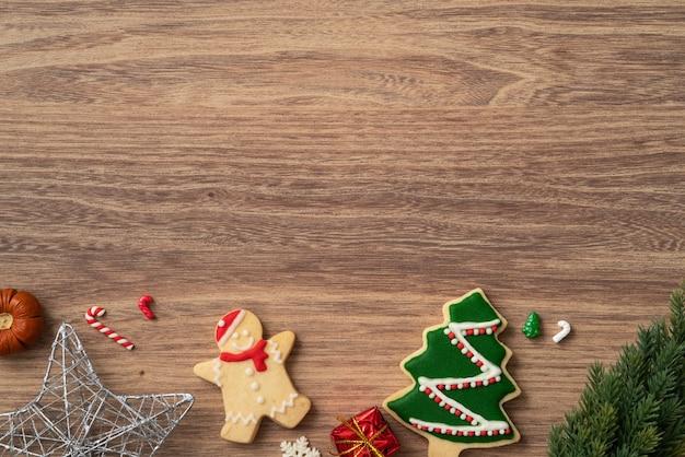 Vista dall'alto di biscotti di panpepato di natale decorati con decorazioni su sfondo di tavolo in legno con spazio di copia, concetto di celebrazione delle vacanze.