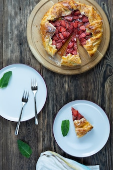 Vista dall'alto di una deliziosa crostata al forno con fragole con piatti e forchette su un tavolo di legno