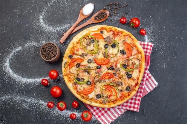 Vista dall'alto deliziosa pizza al formaggio con pomodori rossi su superficie scura