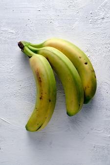 Vista dall'alto di deliziose banane mature colorate sulla superficie del calcestruzzo bianco
