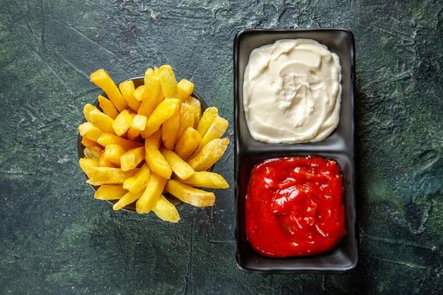 Vista dall'alto deliziose patatine fritte con condimenti sulla superficie scura