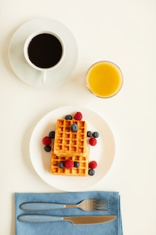 Vista dall'alto alla deliziosa colazione gourmet con cialde dolci da dessert e succo d'arancia accanto alla tazza di caffè nero sul tavolo bianco