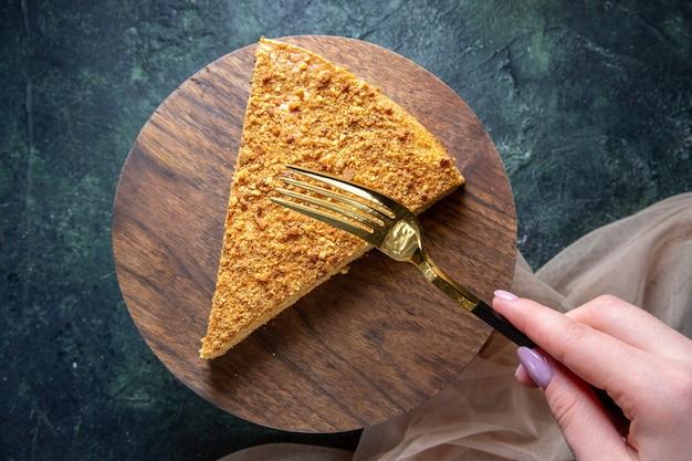 Vista dall'alto deliziosa fetta di torta di miele di esso sulla superficie scura tavola di legno rotonda