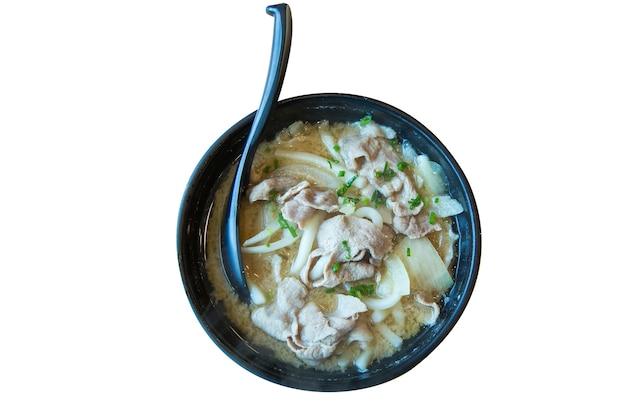 Vista dall'alto di deliziosi ramen giapponesi udon con cucchiaio nella ciotola, messa a fuoco selettiva.