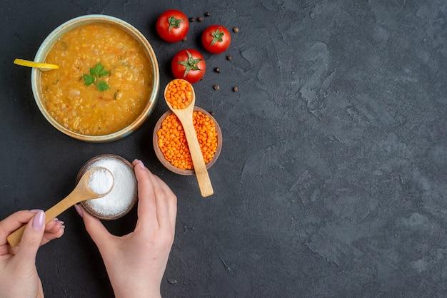 Vista dall'alto deliziosa zuppa di lenticchie con sale che esce da un piccolo piatto e pomodori rossi sulla superficie scura