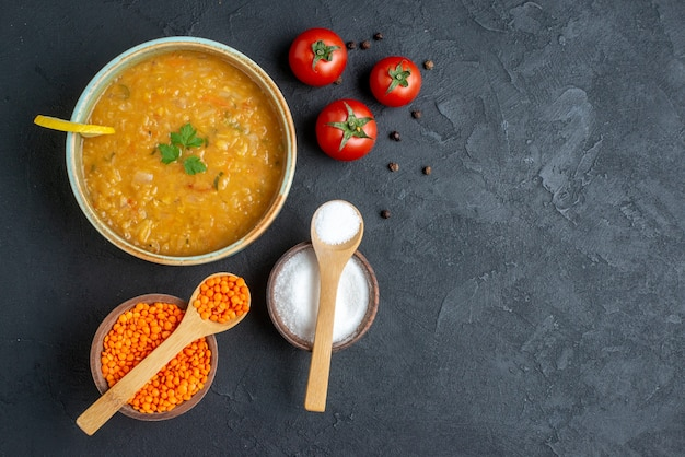 Vista dall'alto deliziosa zuppa di lenticchie con sale e pomodori rossi sulla superficie scura