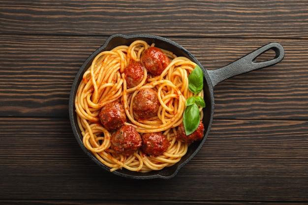 Vista dall'alto di una deliziosa pasta con polpette, salsa di pomodoro e basilico fresco in padella rustica vintage in ghisa servita su tagliere, fondo di legno. gustosi spaghetti di polpette fatti in casa