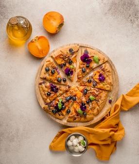 Vista dall'alto di una deliziosa fetta di pizza con petali di fiori e cachi