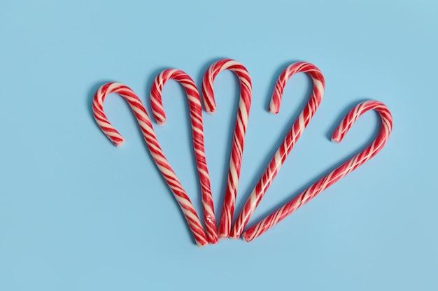 Vista dall'alto di deliziosi bastoncini di zucchero dolci su sfondo blu con spazio copia per la pubblicità natalizia.