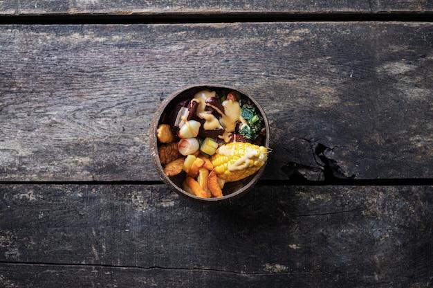 Vista dall'alto di un delizioso pranzo vegano pieno di cereali, verdure e proteine servito in una ciotola di cocco biologico