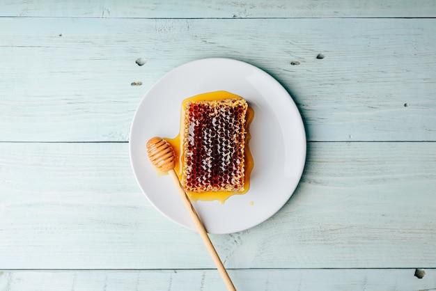 Vista dall'alto del favo delizioso delizioso sul piatto luminoso con mestolo di miele su fondo in legno chiaro