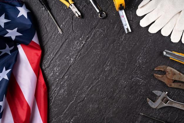 Concetto di design vista dall'alto dell'american labor day con strumenti di lavoro sullo sfondo del tavolo in ardesia.