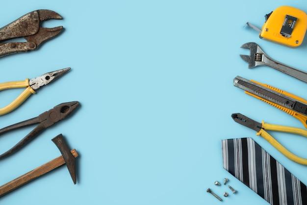 Concetto di design vista dall'alto della festa del papà e festa del lavoro con strumenti di lavoro su sfondo blu.