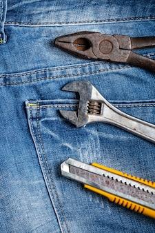 Concetto di design vista dall'alto della festa del lavoro con strumenti di lavoro su sfondo blu jeans.