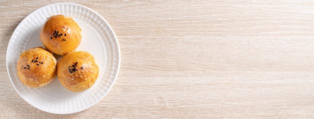 Concetto di design vista dall'alto della pasticceria al tuorlo della torta lunare, torta lunare per le vacanze del festival di metà autunno su sfondo di tavolo in legno