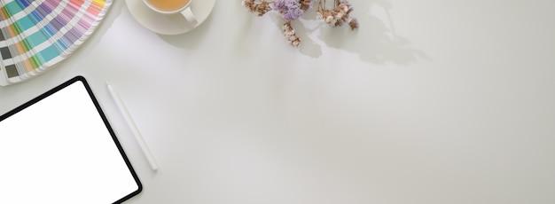 Vista dall'alto del tavolo da lavoro di design con tavolo, campione di colore, tazza di tè e spazio di copia