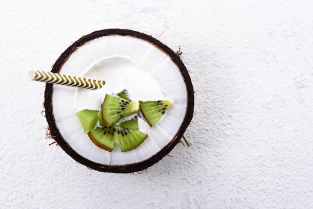 Dessert di vista dall'alto con crema e kiwi nella ciotola di cocco con paglia su sfondo bianco con spazio di copia