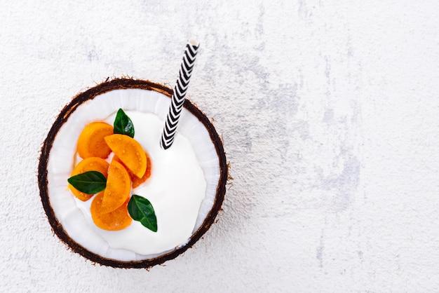 Dessert di vista dall'alto con crema e physalis nella ciotola di cocco con paglia su priorità bassa bianca con lo spazio della copia