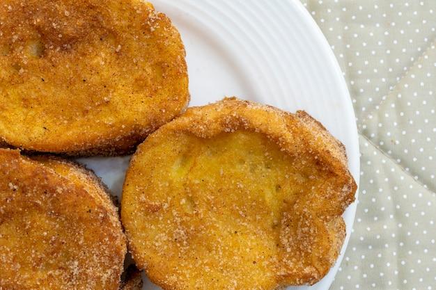 Dettaglio vista dall'alto di pane cotto o fritto con zucchero e cannella. dessert chiamato rabanada, torrija o pane dorato.