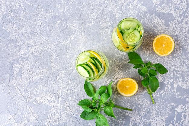 Bevanda di acqua detox vista dall'alto con cetriolo e limone su sfondo grigio chiaro strutturatod