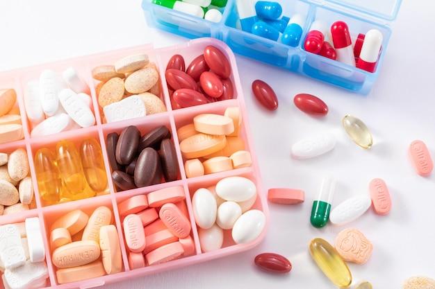 Vista dall'alto di diversi medicinali in un contenitore isolato su una superficie bianca