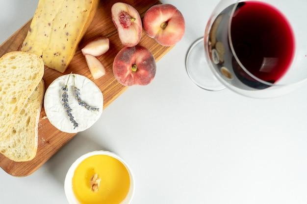 Vista dall'alto diversi tipi di formaggi sul tagliere di legno. formaggio con pesca di fichi, miele, ciabatta e noci, bicchiere di vino rosso. elegante cibo piatto disteso su sfondo grigio. copia spazio. focalizzazione morbida