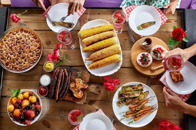 Vista dall'alto su un tavolo da pranzo, decorato con fiori, con stoviglie e cibo. picnic in cortile con amici o vicini, cena in famiglia.