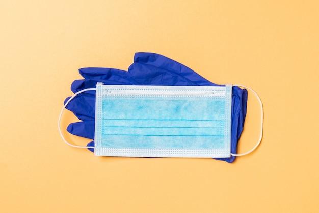 Vista dall'alto della maschera medica usa e getta e guanti in nitrile sulla superficie arancione