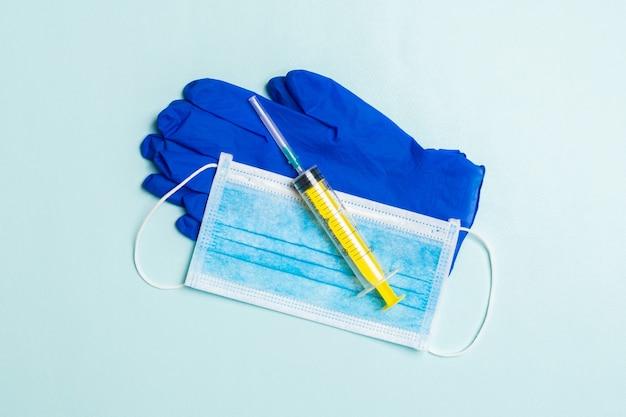 Vista dall'alto della maschera chirurgica usa e getta, un paio di guanti medicali in lattice e una siringa sulla superficie blu
