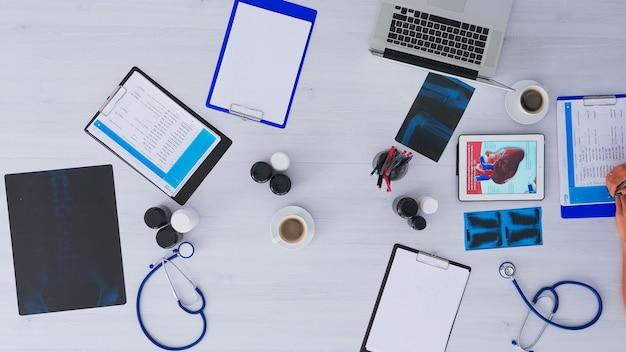 Vista dall'alto del medico che controlla i problemi dei pazienti dagli appunti seduti sul tavolo con raggi x, attrezzature mediche, dispositivi digitali in giro nell'ufficio dell'ospedale