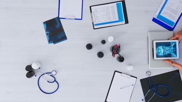 Vista dall'alto del medico che chiude il laptop e analizza i raggi x digitali utilizzando il tablet, lavorando in uno studio medico seduto sulla scrivania con stetoscopio e dispositivi digitali