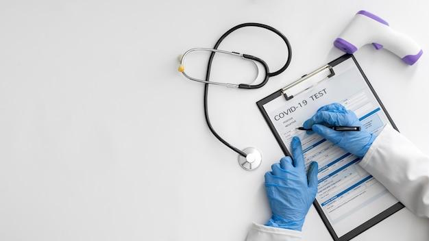 Medico di vista dall'alto che completa il modulo covid