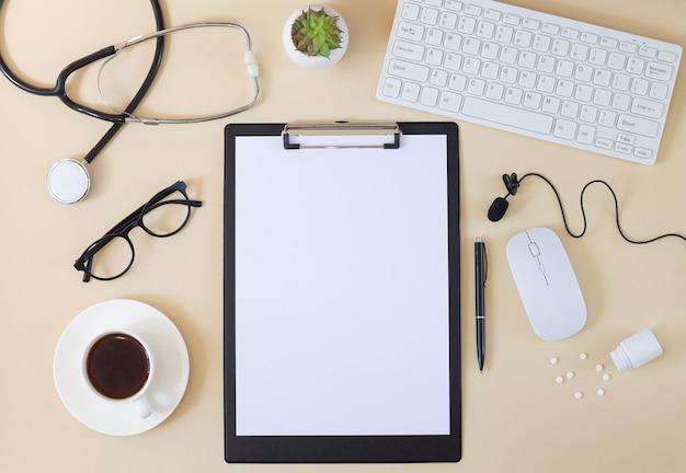 Vista dall'alto del tavolo della scrivania del medico con stetoscopio, appunti, tastiera, microfono, tazza di caffè, pillole, occhiali, ecc. concetto di consultazione medica online