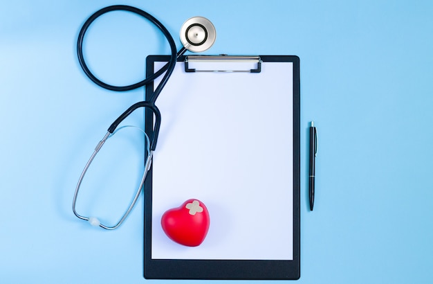Vista dall'alto del tavolo scrivania medico con stetoscopio, cuore rosso, penna e carta bianca negli appunti. concetto di malattie cardiologiche