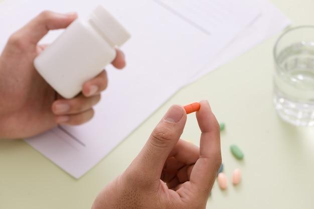 Vista dall'alto della mano di un medico che scrive una prescrizione. sulla scrivania ci sono anche un flacone di pillole e uno stetoscopio.