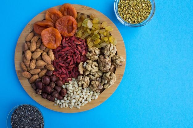 Vista dall'alto di albicocche secche, uvetta, bacche di goji, noci, semi di chia e polline d'api sul tagliere