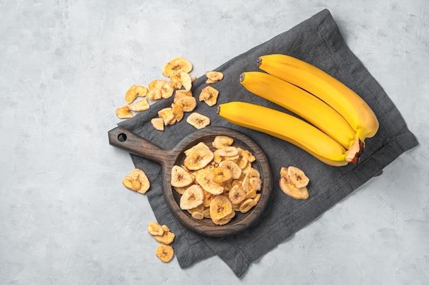 Vista dall'alto di banane secche su un panno da cucina grigio su sfondo di marmo bianco white