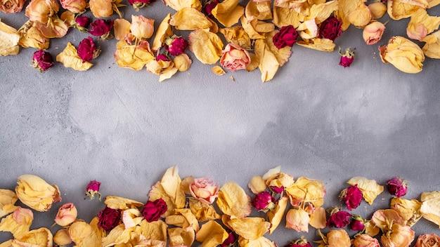 Vista dall'alto della priorità bassa dei fiori secchi con lo spazio della copia. cornice con fiori secchi su sfondo grigio.