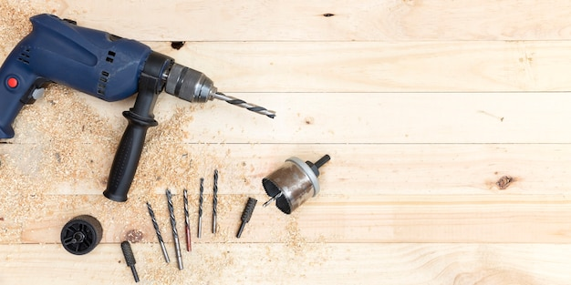 Vista dall'alto di trapano, punte da trapano e accessori per falegnameria su banco da lavoro in legno di pino naturale.