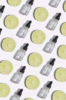 Flacone contagocce vista dall'alto di siero alla vitamina c, olio cosmetico e fette di lime su sfondo bianco. formato verticale del modello di cosmetici creativi
