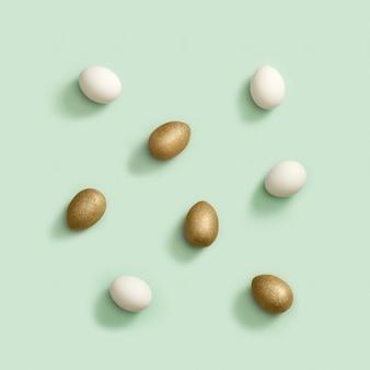 Composizione di pasqua vista dall'alto con uova bianche e dorate, motivo creativo, vacanze di primavera.
