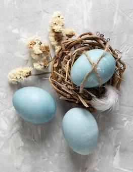 Vista dall'alto di uova di pasqua nel nido di uccelli con piume e fiori