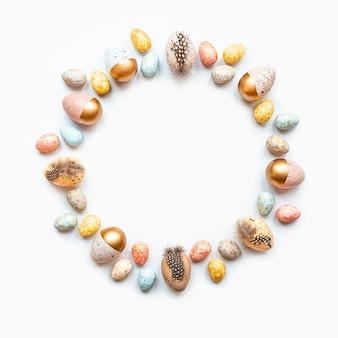 Vista dall'alto di uova di pasqua colorate con vernice dorata disposte in cerchio. sfondo bianco. copia spazio.